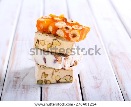 Honey and different sorts of nut nougat slices on wooden table - stock photo