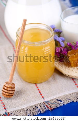 Honey and milk on wooden table close-up