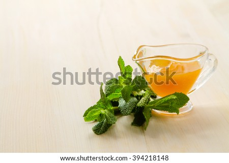 Honey and mint on a white wooden table