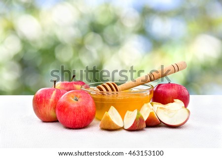 Honey and red apples on table on the blur natural background with space for text