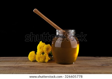 honey and yellow flowers on a black background - stock photo