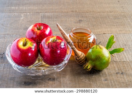 Honey, apples and pomegranates on wood deck for Rosh Hashana celebration. - stock photo