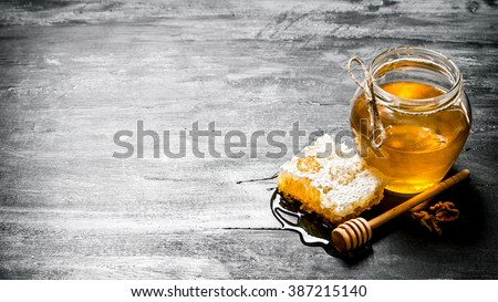 Honey background. Natural honey comb and a glass jar. On black rustic table. - stock photo