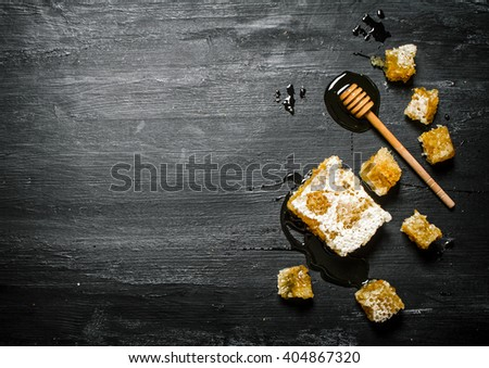 Honey background. Natural honey comb and a wooden spoon . On black rustic table. - stock photo