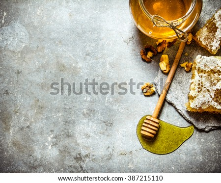 Honey background. Natural sweet honey with shelled walnuts. On the stone table. - stock photo