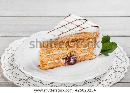 Honey cake with walnuts and cherries on plate, on a light wooden background. Selective focus - stock photo