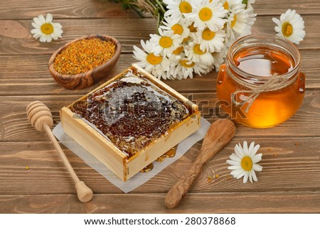 Honey, chamomile and pollen on a brown background - stock photo