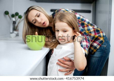 Honey child girl five years old drinking woter from glass under the supervision of a beautiful young woman - stock photo