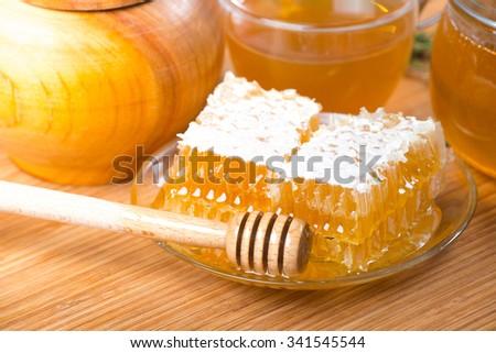 Honey. Closeup of honeycombs wax and honey dipper - stock photo