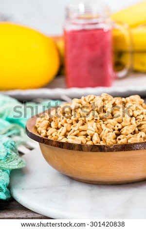 Honey coated puffed wheat breakfast cereal. Fruit background - stock photo