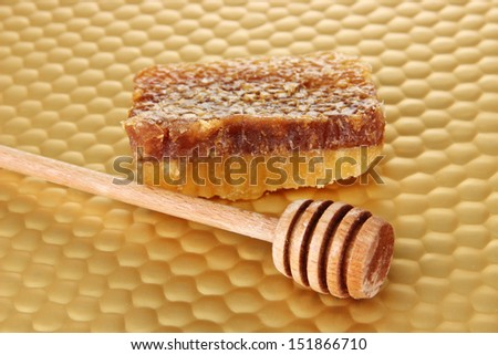 Honey comb and honey on bright yellow background - stock photo