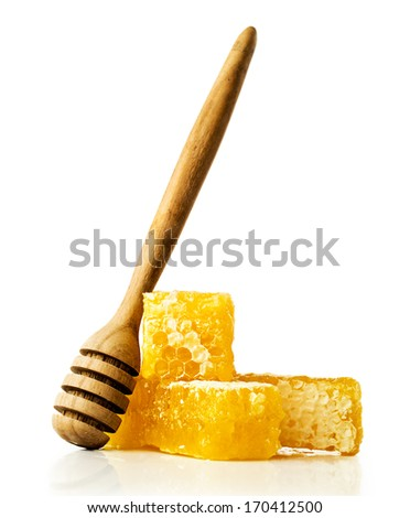 honey comb with a wooden dipper isolated on white - stock photo