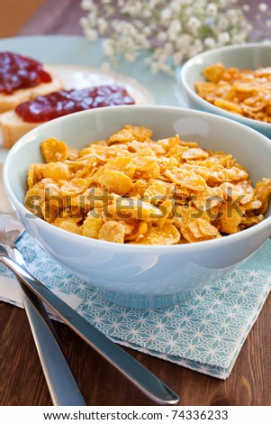 Honey cornflakes and toasts with strawberry jam for breakfast - stock photo