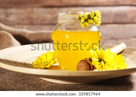 Honey, dipper and flowers on plate on sackcloth - stock photo