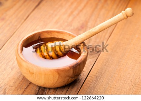 Honey dipper in a wooden bowl