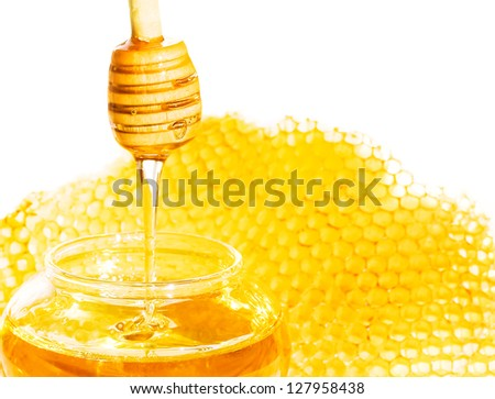 Honey dipper with bee honeycomb isolated on white background. Honey tidbit in glass jar and honeycombs wax. - stock photo