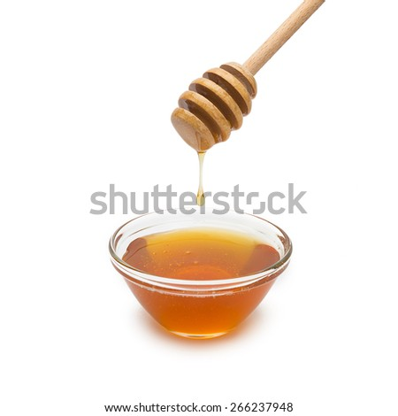 honey dipper with drop of honey floats down in to a glass shell on white background - stock photo