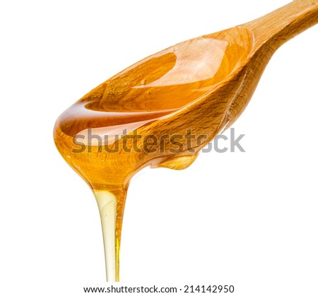 Honey dripping from a wooden honey dipper isolated on white  - stock photo