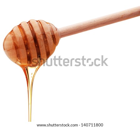 Honey dripping from a wooden honey dipper isolated on white background cutout - stock photo