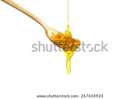 Honey dripping from a wooden spoon - stock photo