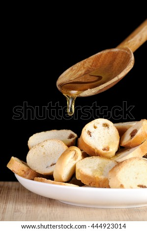 Honey dripping from a wooden spoon on crackers. Isolated on black. - stock photo