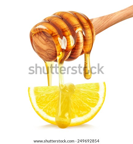 honey dripping on a slice of lemon on a white background - stock photo