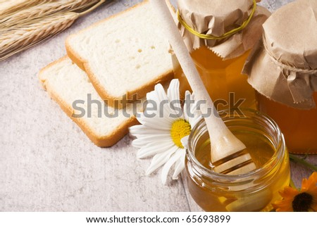 honey, flowers, spike and bread on table
