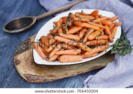 Honey Glazed Baby carrots with an old rustic wooden spoon and thyme. Extreme shallow depth of field with selective focus on carrots in the foreground.
