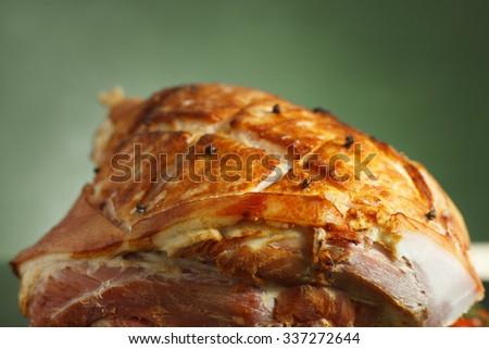 Honey glazed ham on black glossy surface - stock photo
