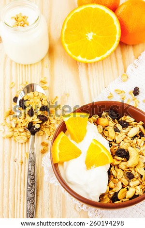 Honey glazed oatmeal, nut and coconut chips granola in a glass bowl with yogurt and oranges on a wooden background - stock photo