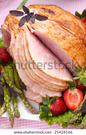 Honey ham on Easter table with eggs, tulips and decoration
