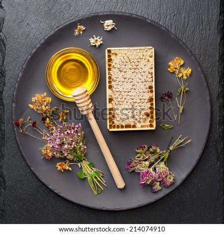 Honey, honeycomb and dried herbs on dark background  - stock photo