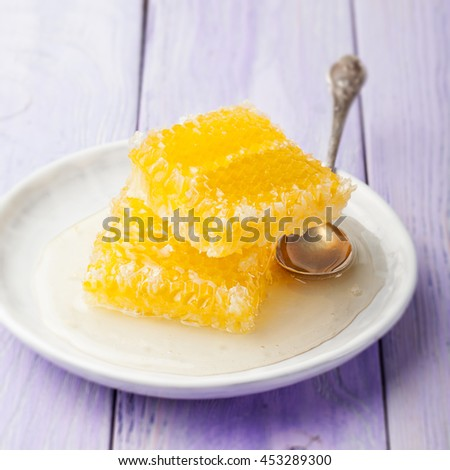 Honey, honeycombs on a lavender wooden background - stock photo