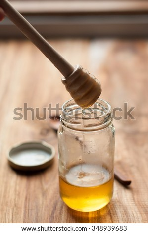 Honey in a bottle with wooden spoon on a wooden background - dripping from spoon