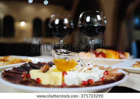 honey in a cup among slicing cheese and sausages - stock photo