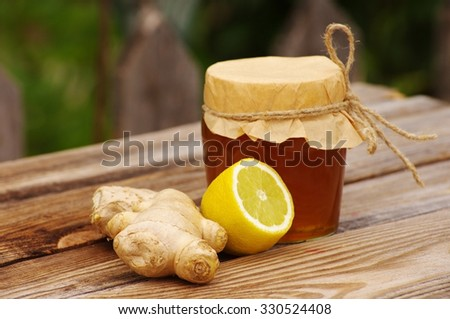 Honey in a glass jar, ginger root, a lemon on a wooden table in a summer sunny day . Honey with  ginger and lemon - stock photo
