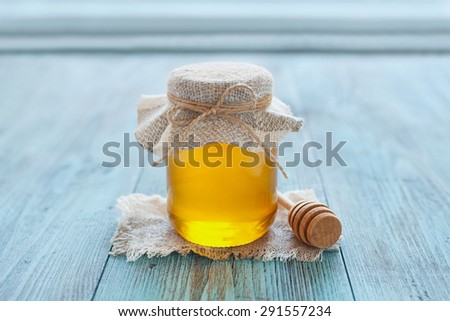 Honey in a pot or jar with twine tied in a bow and honey dipper on a blue wooden background - stock photo
