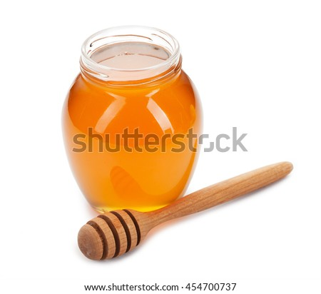 honey in glass and wooden stick isolated on white background.