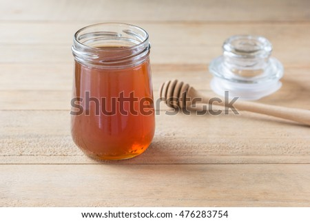 Honey in glass bottle and wooden honey dipper