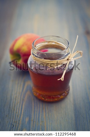 Honey in glass jar and apple on wooden table - stock photo