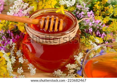 Honey in glass jar close up with wooden spoon and cup of tea on flowers background