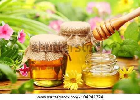 Honey in glass jars with flowers background. - stock photo