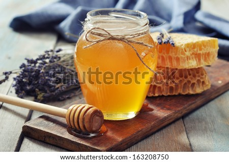 Honey in jar with honey dipper on vintage wooden background  - stock photo