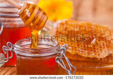 Honey in jar with honeycomb and wooden drizzler - stock photo