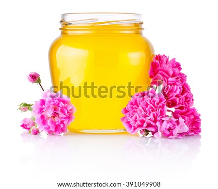 Honey in open glass jar and flowers isolated on white background - stock photo