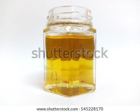 Honey in the bottle glass isolated on white background
