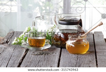 Honey in transparent bank, milk in a jug and tea in a transparent cup on a wooden table