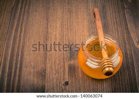 Honey jar on wooden table background. Vintage toned - stock photo