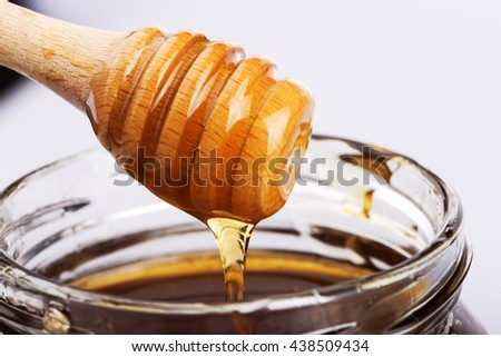 Honey jar with dipper and flowing honey - stock photo