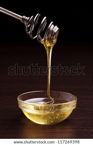 honey jar with steel spoon and flowing honey - stock photo